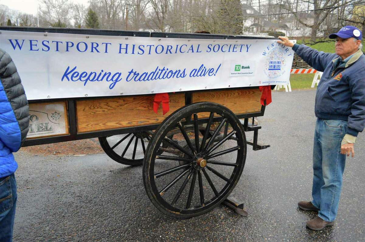 Bob Mitchell, board president, helps prepare a banner on the carriage at the First Light Festival at the Westport Historical Society, Monday, Dec. 31, 2018, in Westport, Conn.