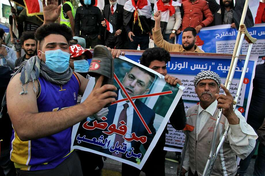 """A protester hits a poster with a defaced picture of Asaad al-Eidani, Iran-backed parliamentary bloc's nominee for the post of the prime minister and Arabic that reads """"rejected by the people,"""" with a shoe during anti-government demonstrations in Baghdad, Iraq, Thursday, Dec. 26, 2019. Iraq's president refused Thursday to designate Asaad al-Eidani for the post of prime minister after he was rejected by anti-government protesters and said he was ready to submit his resignation to Parliament. (AP Photo/Khalid Mohammed) Photo: Khalid Mohammed, Associated Press"""