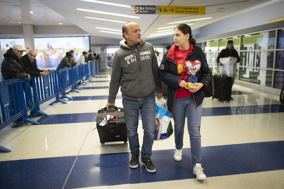 In this Tuesday, Dec. 3, 2019, photo Mohammed Hafar, left, helps his daughter Jana with her luggage as they leave JFK Airport in New York. Jana had been forced by President Donald Trump's travel ban to stay behind in Syria for months while her father, his wife and son Karim started rebuilding their lives in Bloomfield, N.J., with no clear idea of when the family would be together again. Mohammed was part of a federal lawsuit filed in August of this year over the travel ban waiver process. (AP Photo/Mary Altaffer) Photo: Mary Altaffer, Associated Press