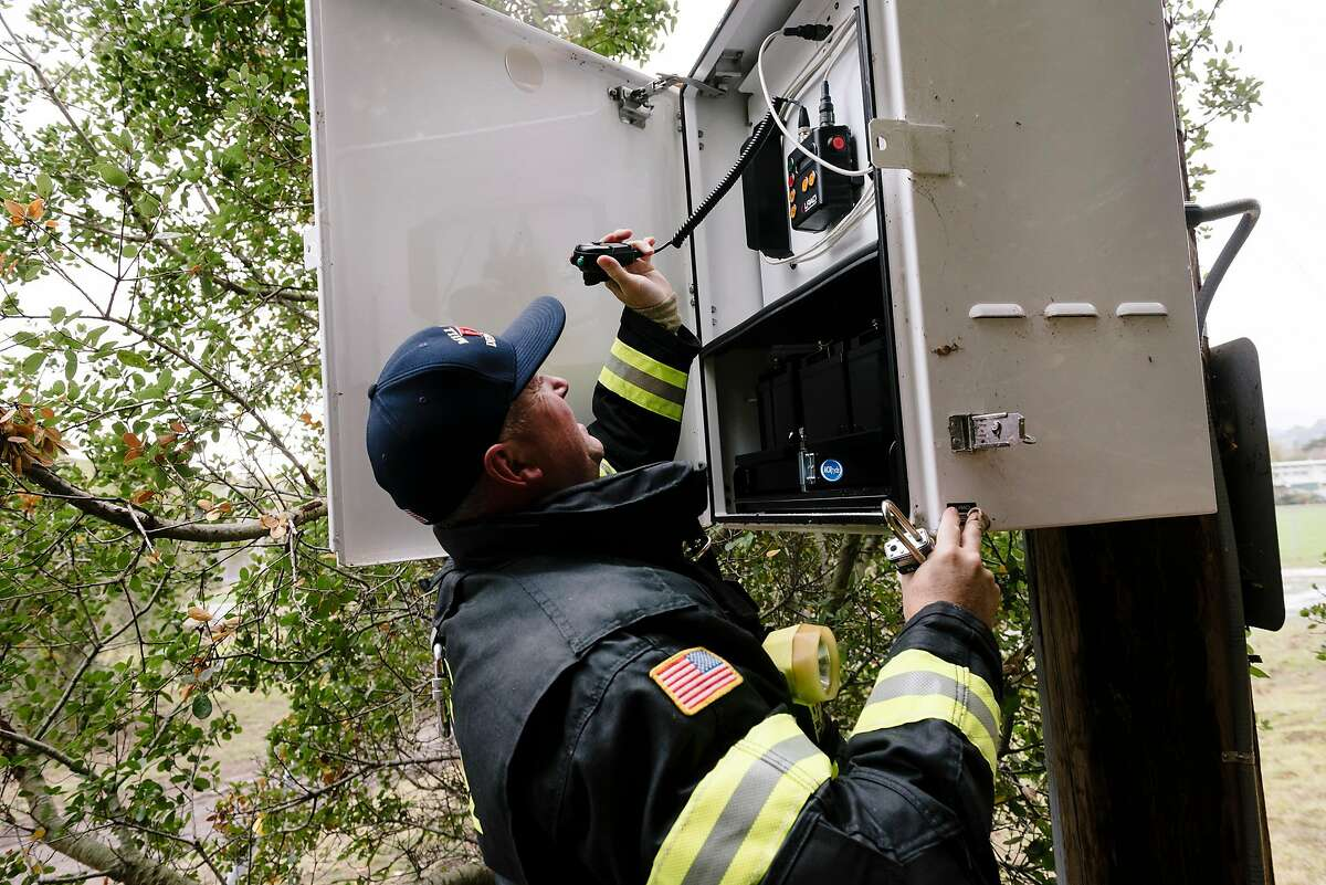 Mill Valley Fire Department Battalion Chief Scott Barnes, shows a microphone and battery backup inside one of Mill Valley's five new LRAD satellite-based siren notification emergency systems in Mill Valley, California, Saturday, December 7th, 2019.