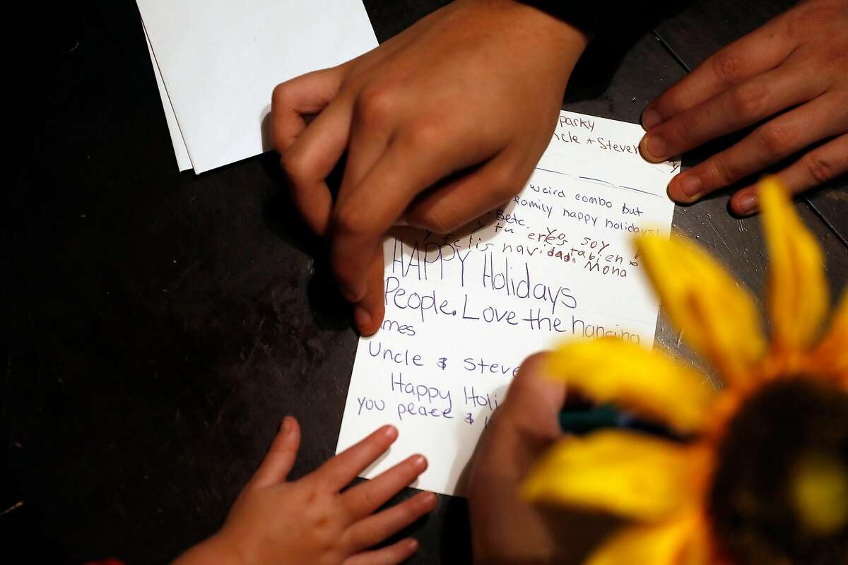 Jessica Vega writes a Holiday card with her children at her home in Santa Rosa, Calif., on Monday, December 23, 2019.