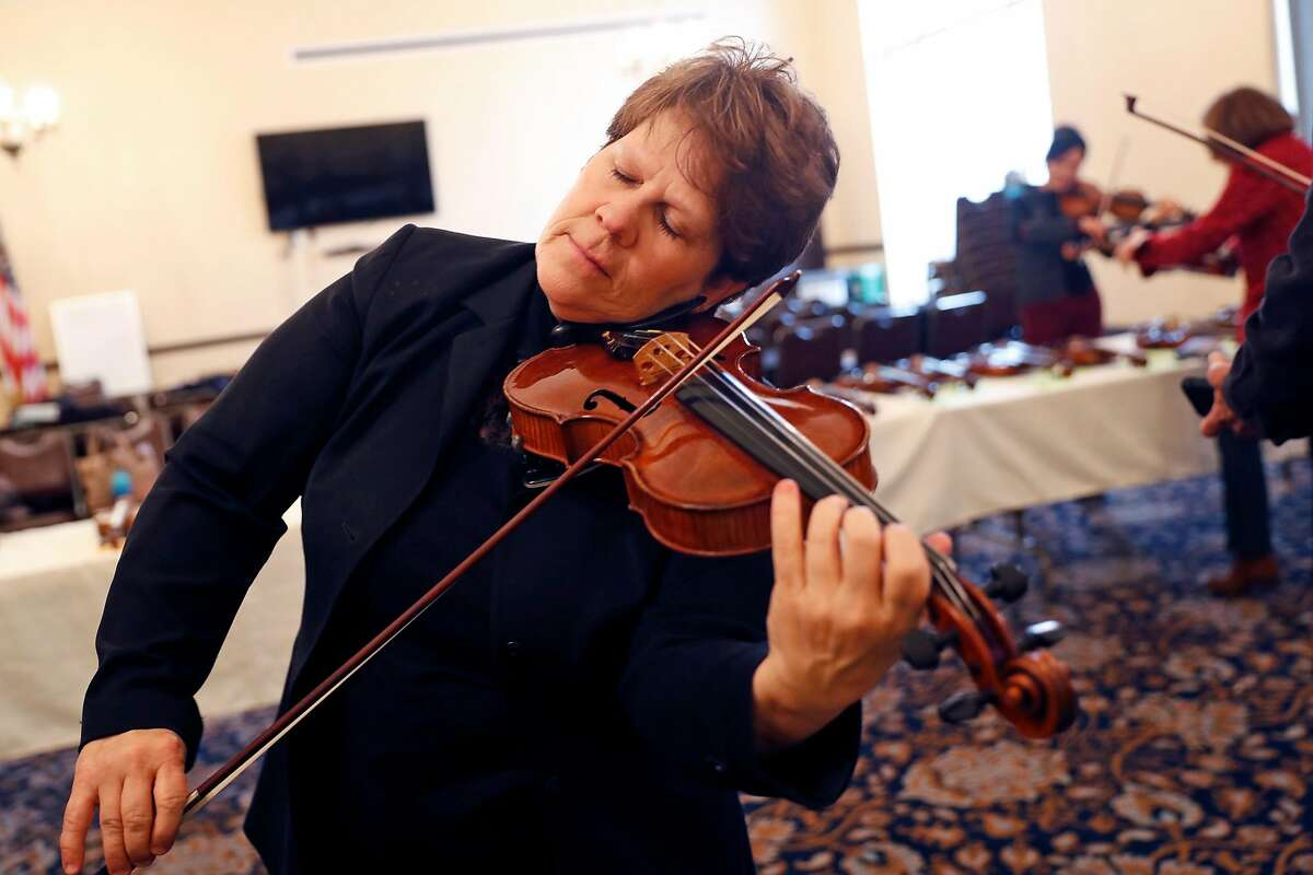 San Francisco Opera Orchestra string quartet member Dawn Harms tests a violin from Violins of Hope, a multi-organizational project built around a collection of violins that were played in concentration camps and ghettos during the Holocaust, at Veteran's Building in San Francisco, Calif., on Wednesday, December 18, 2019.