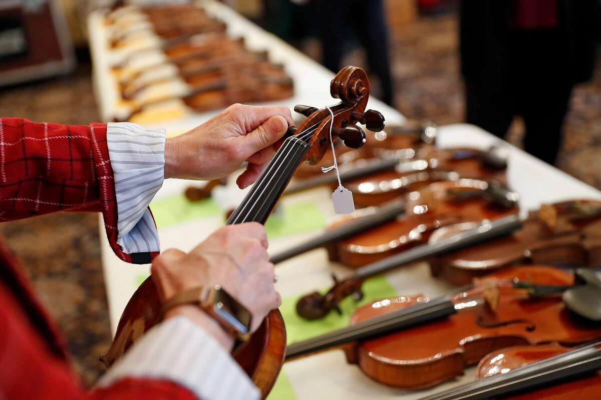 Cookie Segelstein tunes a violin from Violins of Hope, a multi-organizational project built around a collection of violins that were played in concentration camps and ghettos during the Holocaust, at Veteran's Building in San Francisco, Calif., on Wednesday, December 18, 2019.