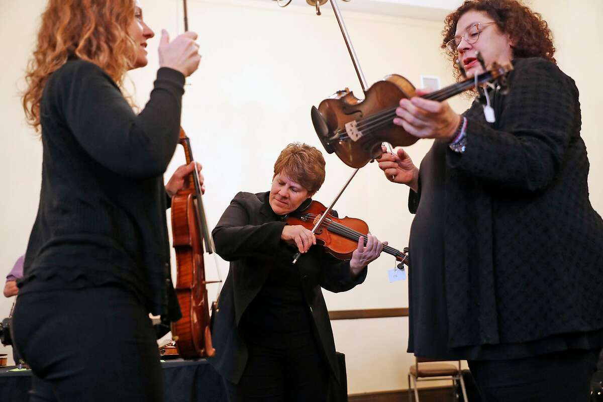 (left to right) San Francisco Opera Orchestra string quartet members Elizabeth Prior, Dawn Harms and Kay Stern test violins from Violins of Hope, a multi-organizational project built around a collection of violins that were played in concentration camps and ghettos during the Holocaust, at Veteran's Building in San Francisco, Calif., on Wednesday, December 18, 2019.
