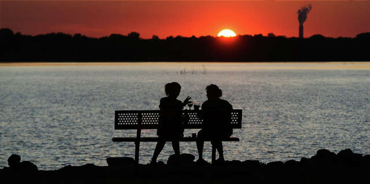 """Two women enjoy themselves, looking out over the Mississippi River at the Lincoln Shields Recreation Area in West Alton, Missouri. River Travel Magazine has named Alton the """"Mississippi River's Best Hidden Gem."""" It also listed Elsah and Alton among the """"Best Holiday River Towns"""" from northern Minnesota to the Gulf of Minnesota."""