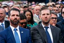 FILE -- Donal�d Trump Jr., left, and Eric Trump during a ceremony at the Normandy American Cemetery in Colleville-sur-Mer, France, June 6, 2019. Office towers in New York and San Francisco - centers of political resistance - are offsetting revenue downturns in the president's glitzier Trump-branded hotels. (Doug Mills/The New York Times)
