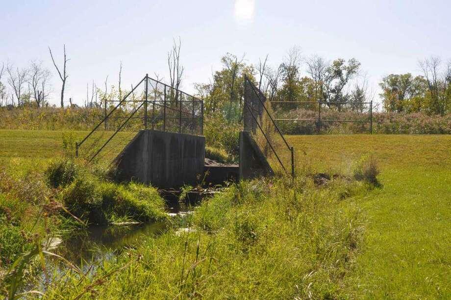 The grass-covered earthen dam near Fox Hill condominiums. Photo: Macklin Reid / Hearst Media Connecticut
