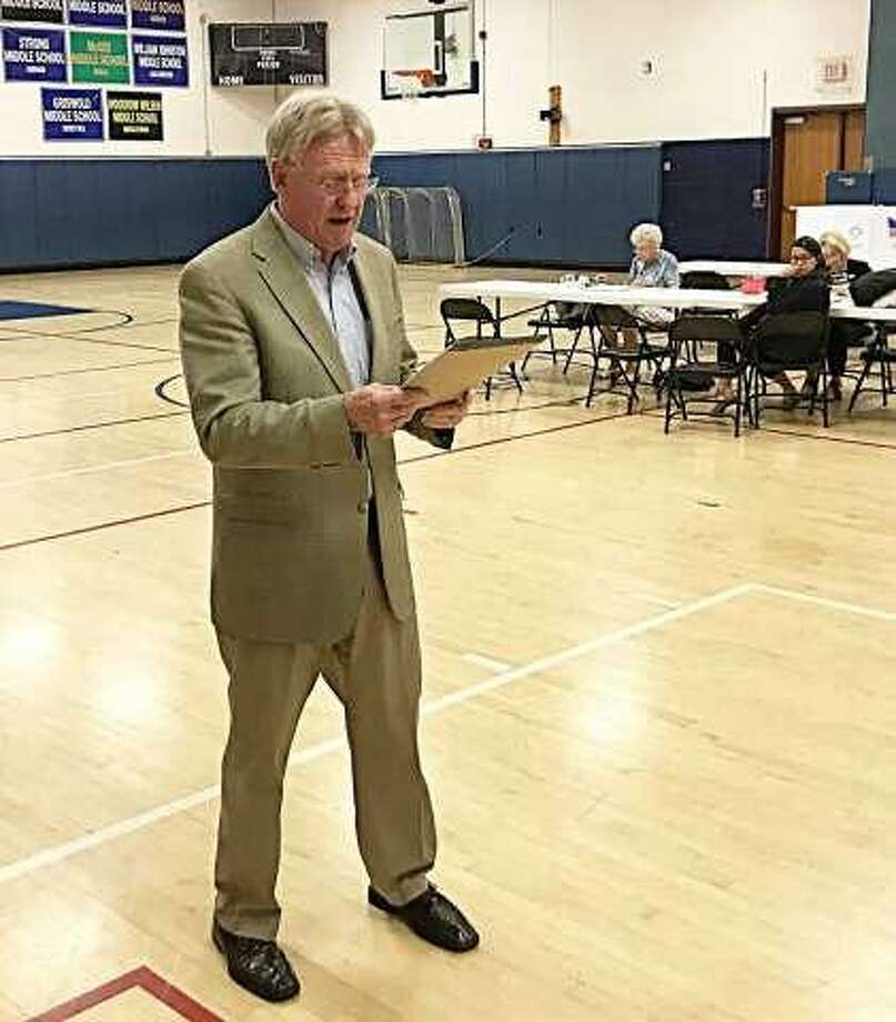 """Then East Hampton election moderator Robert """"Red"""" McKinney reads the budget vote totals Tuesday evening at the middle school. McKinney died Dec. 24. Photo: /"""