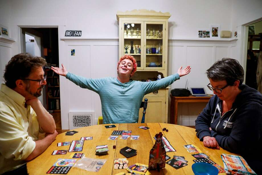 High school senior Philip Wolf plays a board game with his parents, Martin (left) and Hannah Wolf, in San Francisco in October. Photo: Gabrielle Lurie / The Chronicle
