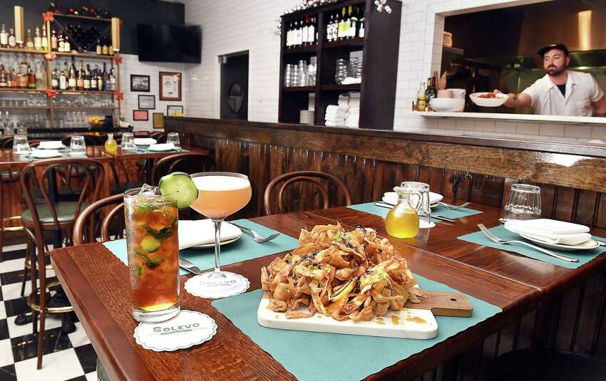 A pair of cocktails, a whiskey sour, left,and a CBD Pimms Cup with an order of eggplant chips at Solevo Kitchen + Social on Phila Street Thursday Dec. 6, 2018 in Saratoga Springs, NY. (John Carl D'Annibale/Times Union)