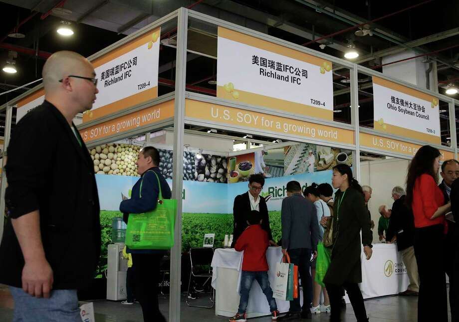 FILE - In this April 12, 2018, file photo, visitors walk by U.S. soybean companies' booths at the international soybean exhibition in Shanghai, China. President Donald Trump likes to joke that America's farmers have a nice problem on their hands: They're going to need bigger tractors to keep up with surging Chinese demand for their soybeans and other agricultural goods under a preliminary deal between the world's two largest economies. Yet skeptics are questioning how much China has committed to buy. (AP Photo/Andy Wong, File) Photo: Andy Wong / Copyright 2018 The Associated Press. All rights reserved.