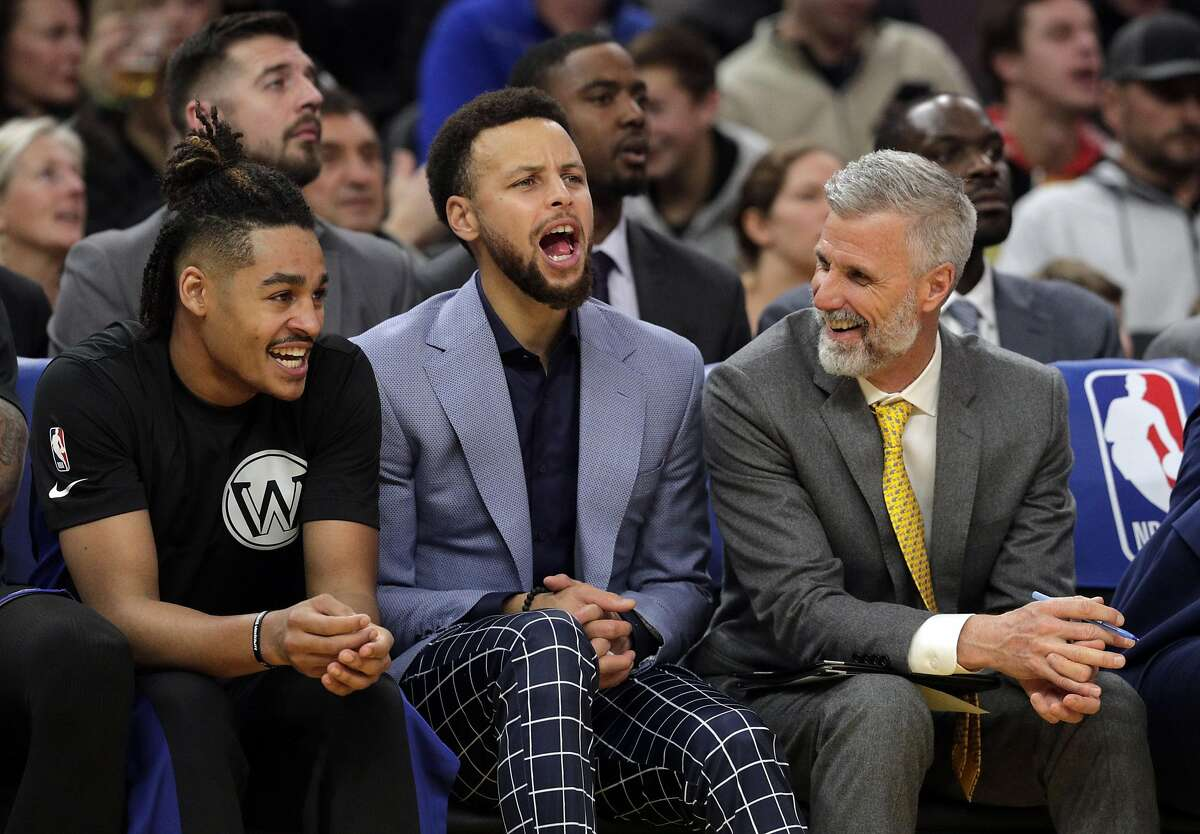 Stephen Curry (30) cheers from the bench with Jordan Poole (3) and coach Bruce Fraser in the second half as the Golden State Warriors played the Houston Rockets at Chase Center in San Francisco, Calif., on Wednesday, December 25, 2019.
