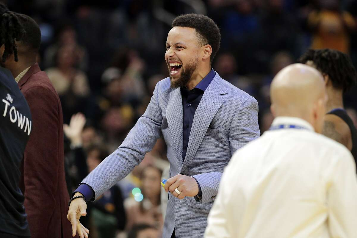 Stephen Curry (30) cheers from the bench in the second half as the Golden State Warriors played the Houston Rockets at Chase Center in San Francisco, Calif., on Wednesday, December 25, 2019.
