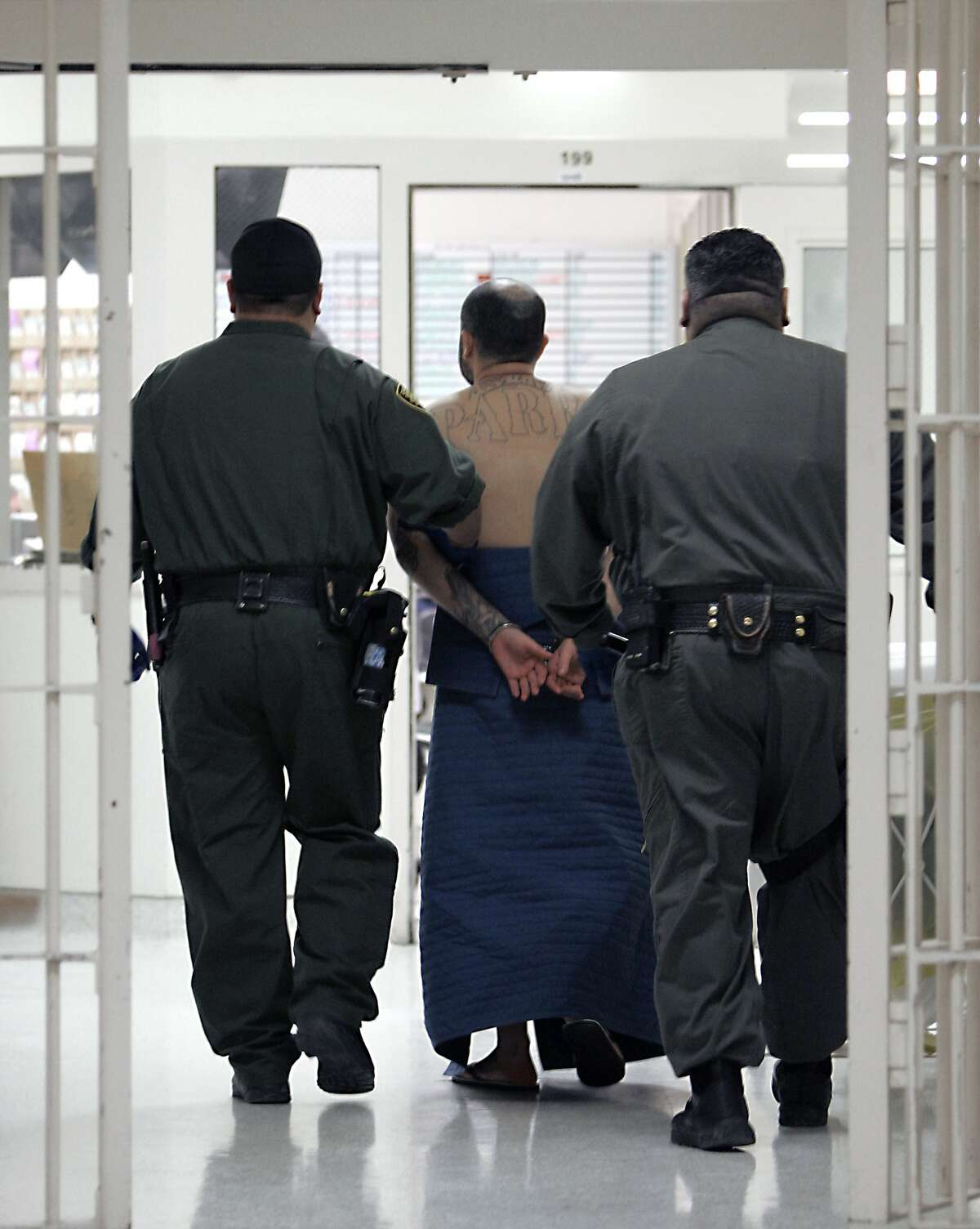 FILE- In this Jan. 14, 2009 file photo, an inmate, on suicide watch, is escorted by correctional officers at the California Substance Abuse Treatment Facility in Corcoran, Calif. A federal judge's special investigator reported Friday, May 3, 2019, that California prison officials provided misleading data on inmate mental health care, but found no intent to do so deliberately. Former U.S. Attorney Charles Stevens substantiated many of the allegations contained in a 161-page whistleblower report last year by Dr. Michael Golding, the prison system's chief psychiatrist. (AP Photo/Rich Pedroncelli, File)