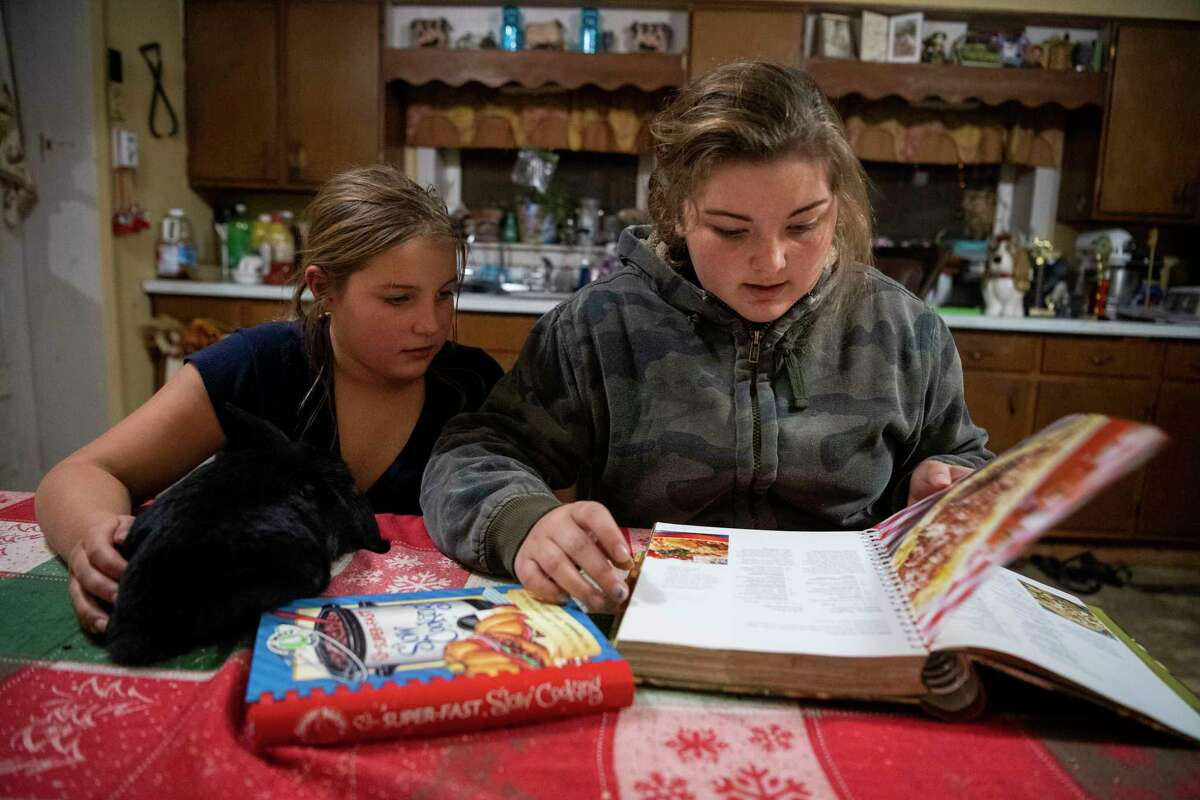 Brooke Lee, 9, holds her rabbit while she helps her sister Paige Lee, 13, look for a recipe to cook Dec. 3 in the kitchen at the Lee family's dairy farm in Berkshire, N.Y.