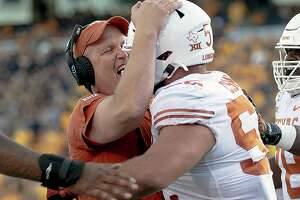 Texas offensive line coach Herb Hand, left, must suddenly replace tackle Sam Cosmi, who opted out of the Longhorns' final two regular-season games to focus on the NFL draft.