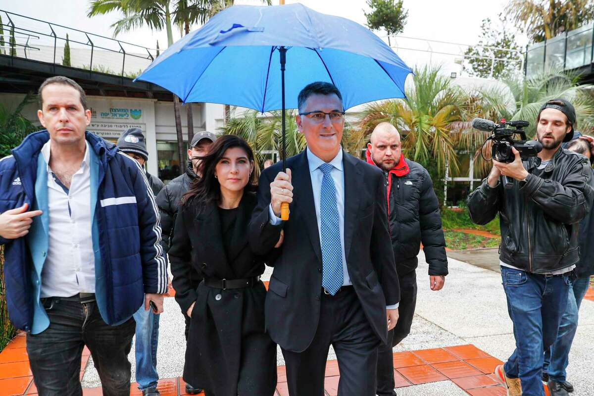 Gideon Sa'ar (C-R), Israeli Member of Knesset for Likud, accompanied by his wife Geula Even Sa'ar (C-L), leave the polling station after casting his ballot during a primary election vote to elect the party chairman, in the coastal city of Tel Aviv, on December 26, 2019. - Sa'ar is the only challenger for incumbent Prime Minister Benjamin Netanyahu for the Likud party leadership ahead of the scheduled general elections in 2020. (Photo by JACK GUEZ / AFP) (Photo by JACK GUEZ/AFP via Getty Images)