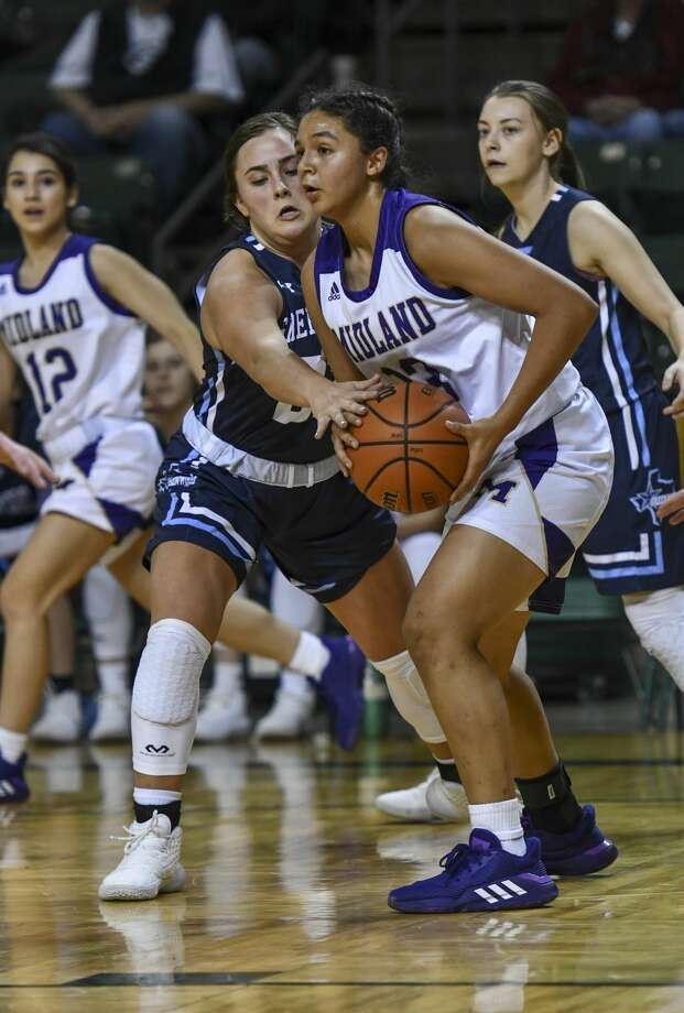 Greenwood's Kensleigh Ellis attempts to grab the ball from Midland High's Noemi Arciga on Thursday, Dec. 26, 2019 at Chaparral Center. Photo: Jacy Lewis/Reporter-Telegram