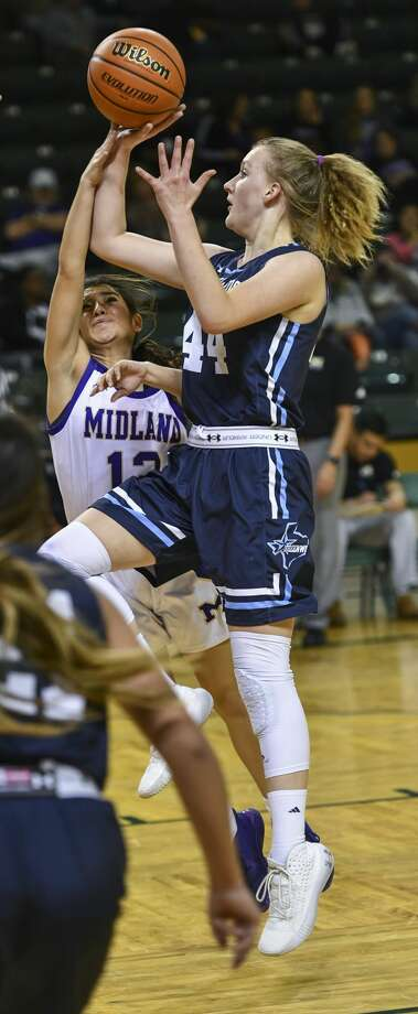 Greenwood's Madeleine Mathes shoots the ball as Midland High's Lauren Jones tips the ball Thursday, Dec. 26, 2019 at Chaparral Center. Photo: Jacy Lewis/Reporter-Telegram
