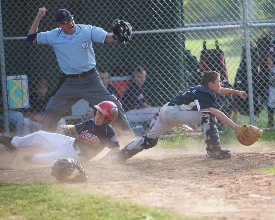 Danbury's Eric Cerno is forced out at home plate on a throw to Exeter catcher Garrett Fosher during Cal Ripken 11-year-old New England Regional Tournament play Wednesday in New Milford. Photo: Barry Horn / The News-Times Freelance