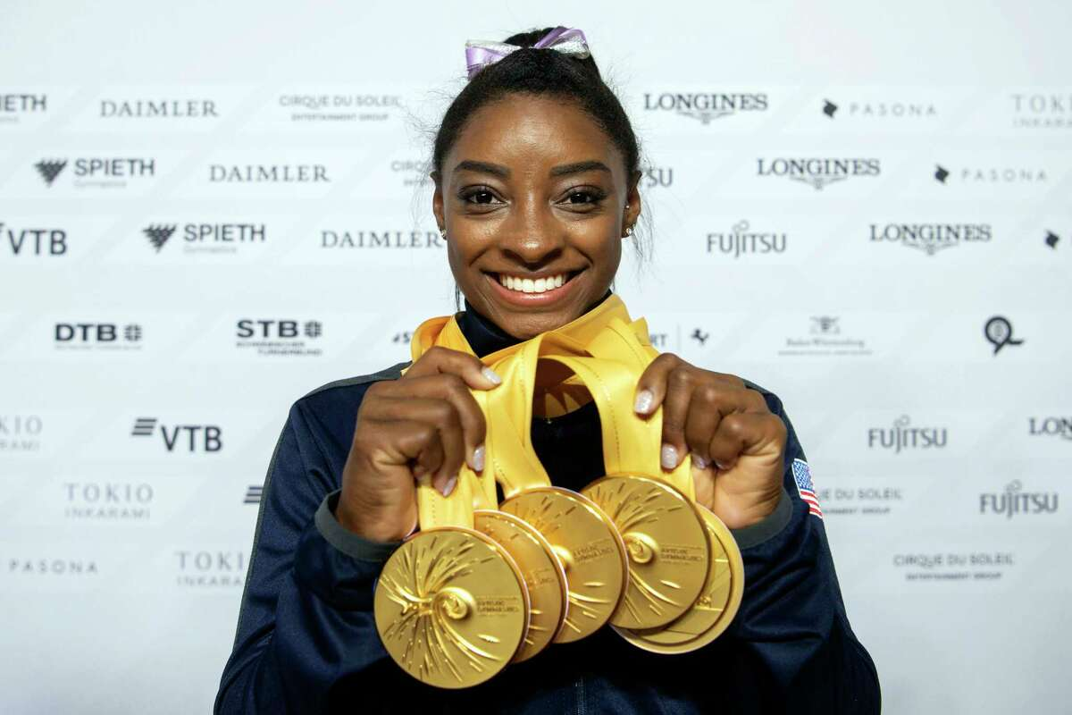 File-This Oct. 13, 2019, file photo Simone Biles of the United States shows her five gold medals at the Gymnastics World Championships in Stuttgart, Germany. Biles is the 2019 AP Female Athlete of the Year. She is the first gymnast to win the award twice and the first to win it in a non-Olympic year. (Marijan Murat/dpa via AP, File)