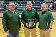 East Chambers head basketball coach Todd Sutherland, center, holds his celebratory plaque as he stands with school superintendent Scott Campbell and his brother and school athletic director Russ Sutherland. East Chambers High School celebrated basketball head coach Todd Sutherland's 800th career win with a ceremony and plaque at the beginning of their game onThursday, December 26, 2019. Fran Ruchalski/The Enterprise