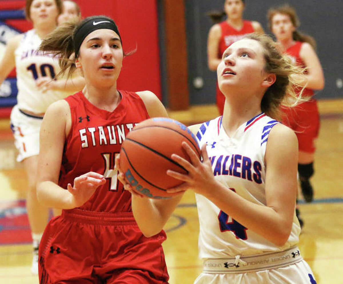 Carlinville's Jill Stayton (right) goes in for a layup off the break ahead of Staunton's Analise Best on Thursday at the Carlinville Tourney.