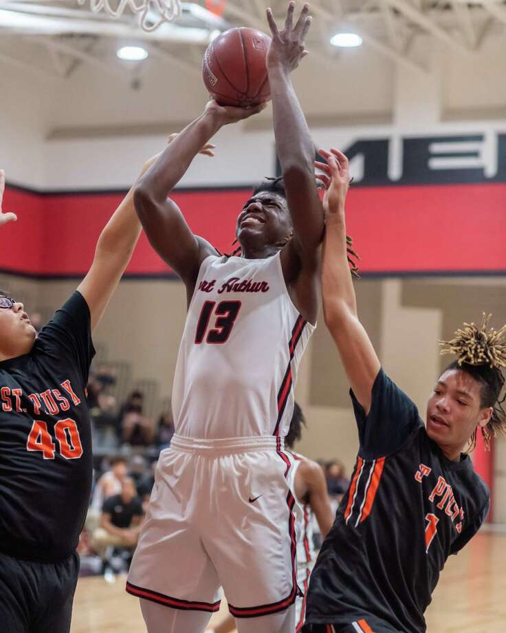 Titans' Nathan Clover (13) fights to put up a shot between Panthers' Elijah Guel (40) and Jamikah Chevis (1) as Port Arthur Memorial downed Pious X in first round action of the 27th Gamble Classic onThursday, December 26, 2019. Fran Ruchalski/The Enterprise Photo: Fran Ruchalski/The Enterprise