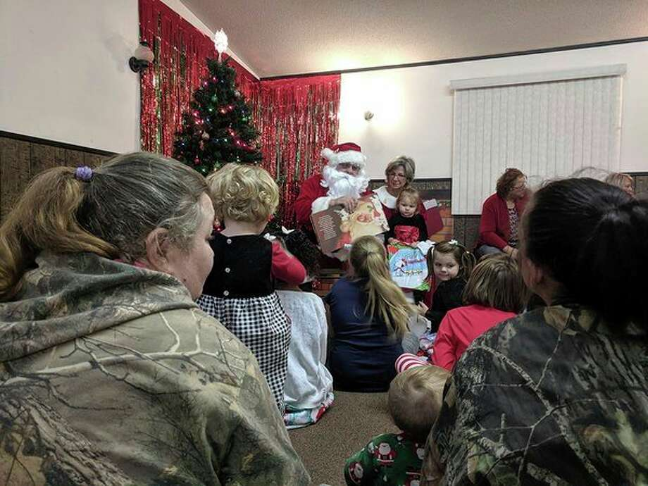 Children listen intently to a holiday story with Santa and Mrs. Claus (Photo provided/Mid Michigan College)