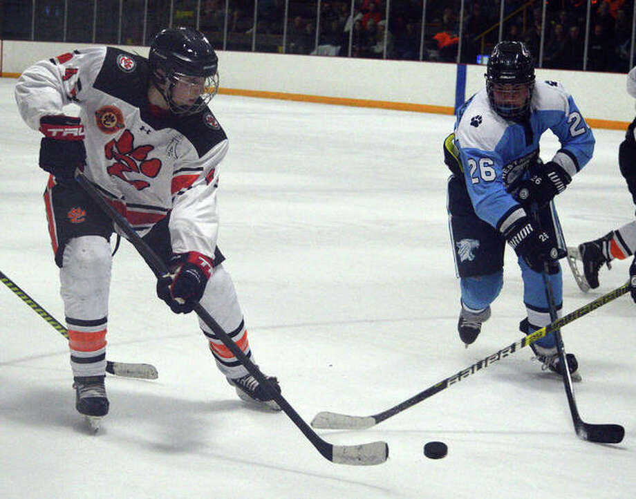 Edwardsville's Parker Terch, left, tries to get past a Westminster defender during the third period of Thursday's game at the East Alton Ice Arena. Photo: Scott Marion/The Intelligencer