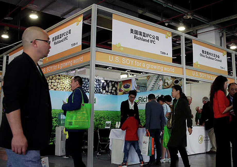 Visitors walk by U.S. soybean companies' booths at the international soybean exhibition in Shanghai, China. President Donald Trump likes to joke that America's farmers have a nice problem on their hands: They're going to need bigger tractors to keep up with surging Chinese demand for their soybeans and other agricultural goods under a preliminary deal between the world's two largest economies. Yet skeptics are questioning how much China has committed to buy. Photo: Andy Wong | AP