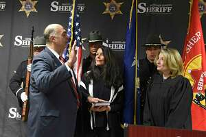 Sheriff Patrick Russo, left, is sworn in by Judge Jill Kehn as Russo's wife Amy holds the Bible during a swearing in ceremony for a second term at the Rensselaer County Jail on Friday, Dec. 27, 2019 in Troy, N.Y. (Lori Van Buren/Times Union)