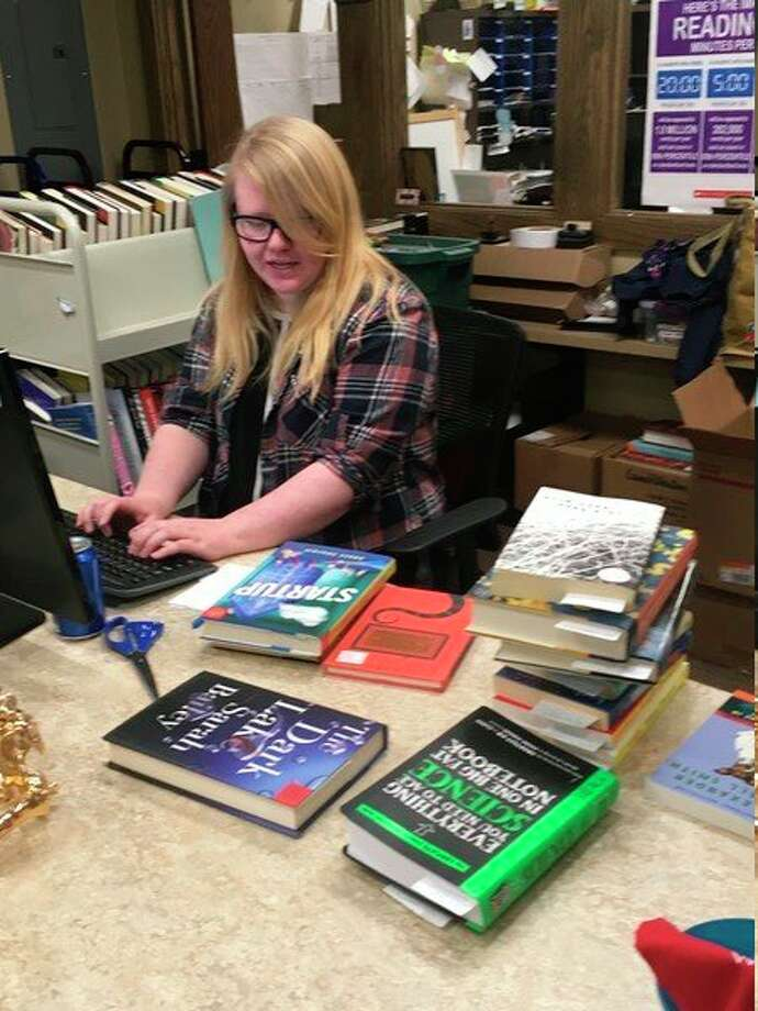 Sarah Welch, the head of programs and services at the Big Rapids Community Library, is pictured working Friday. The library is offering amnesty on fines in January. (Pioneer photo/Tim Rath)