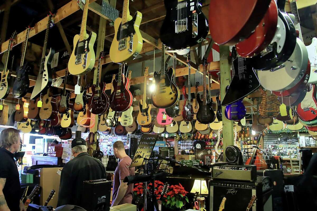 """Musical instruments and equipment fill every space on the floor and the rafters at the Music Factory in Pearland. """"We're a small business but filled to the gills,"""" manager Chase Townshend says."""