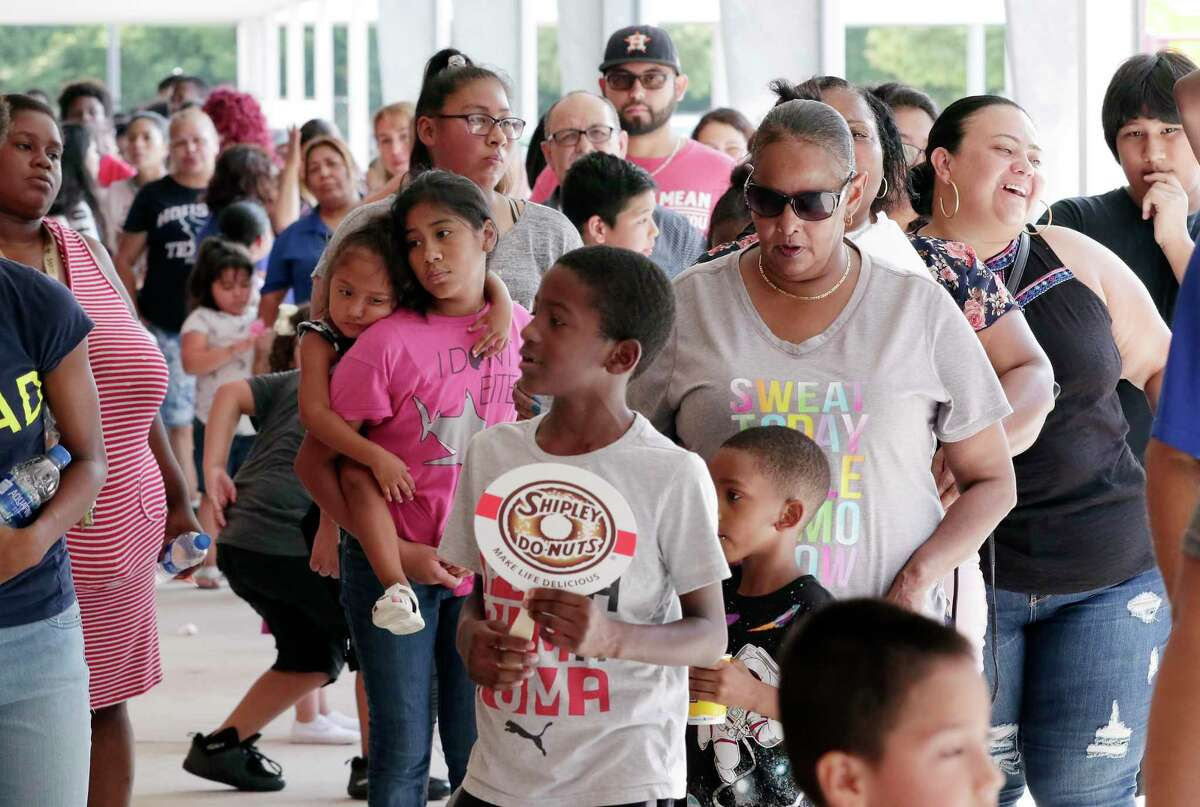 Reagan K-8 students and their parents wait in line outside on the campus before the doors open for the 3rd Annual Returning 2 Learning, a school supplies give away for a specific HISD school through the WithMerci Foundation, created by Houston Texans star Whitney Mercilus, Friday, Aug. 16, 2019 in Houston, TX.