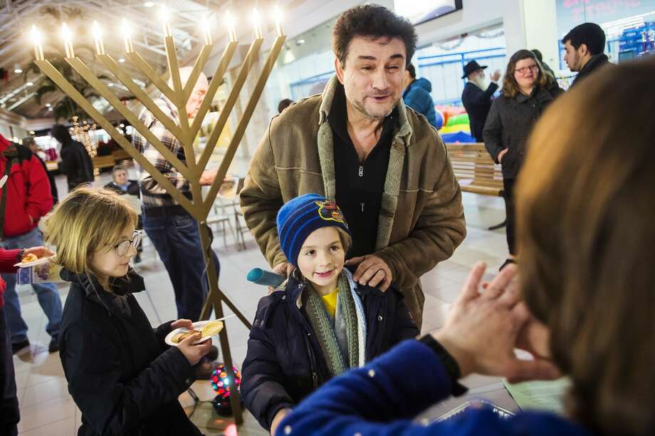Greg Kleynberg of Bay City, right, chats with Shainie Weingarten, foreground, as he stands with his grandchildren, Eli Cicci, 6, center, and Maya Cicci, 9, left, during a Hanukkah celebration, hosted by Chabad of Eastern Michigan, Monday, Dec. 23 at the Midland Mall. Guests enjoyed latkes, music and the lighting of the menorah. (Katy Kildee/kkildee@mdn.net) Photo: (Katy Kildee/kkildee@mdn.net)