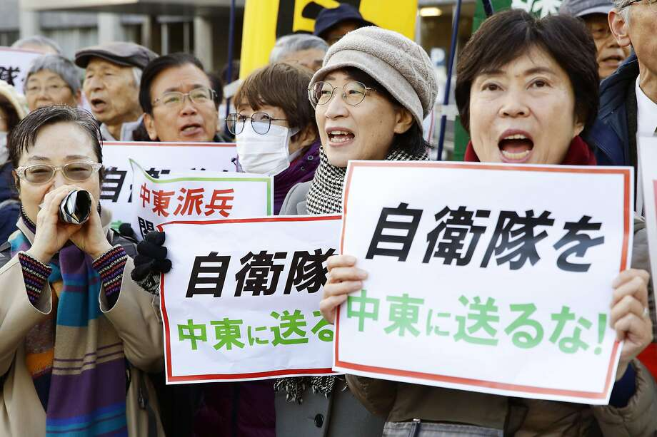 """Protesters hold placards reading """"Do not send Japan's Self-Defense Forces to Middle East"""" in Tokyo. Photo: Hiroki Yamauchi / Associated Press"""