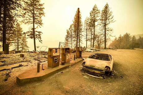 """(FILES) In this file photo taken on November 11, 2018 A burnt car and a gas station remain visible after the """"Camp"""" fire tore through the region near Pulga, east of Paradise, California. - California's governor has rejected a plan by the state's largest utility to emerge from bankruptcy, which included a $13.5 billion payout for victims of a series of wildfires blamed on the company's faulty equipment. Governor Gavin Newsom said in a letter to Pacific Gas and Electric CEO William Johnson on December 13, 2019 that the plan """"falls woefully short"""" of a state law requiring organizational changes and """"a capital structure that allows the company to make critical safety investments."""" (Photo by Josh Edelson / AFP) (Photo by JOSH EDELSON/AFP via Getty Images)"""