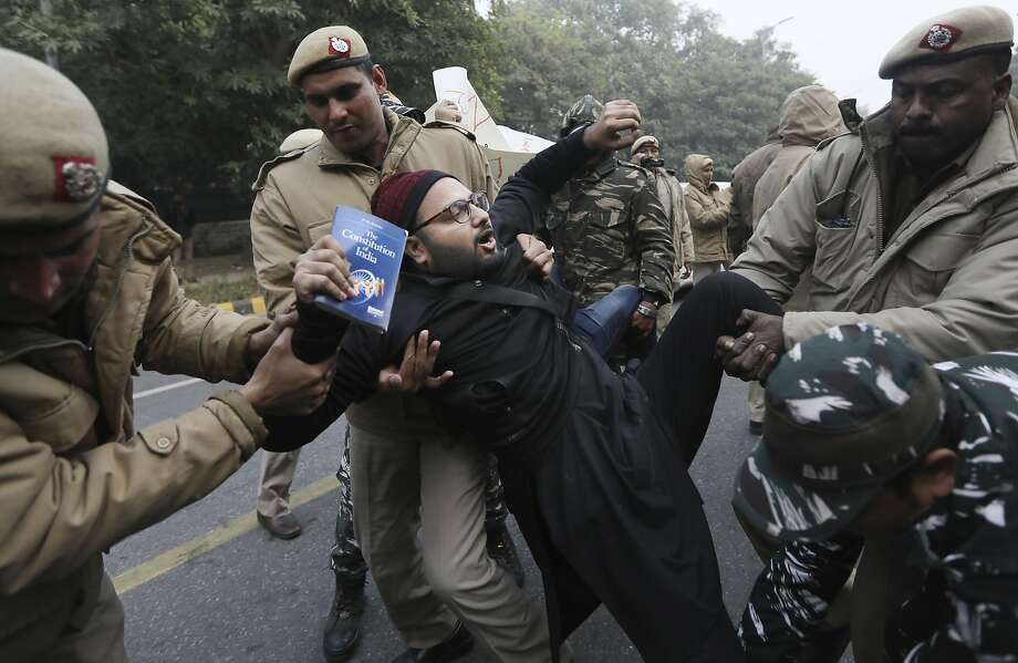 Policemen detain a protesting student, who is holding a book on the Indian constitution in New Delhi. Photo: Manish Swarup / Associated Press