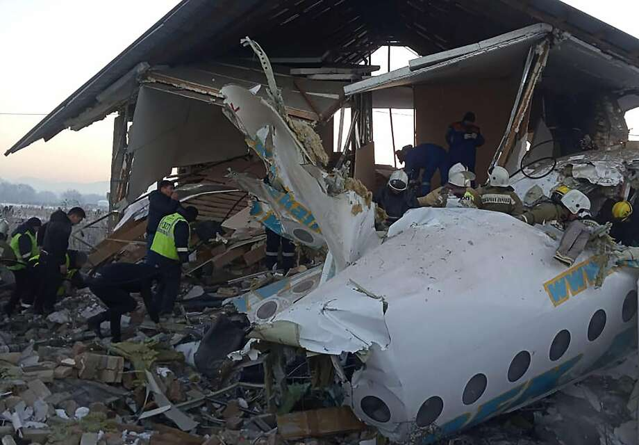 A Bek Air Fokker 100 passenger plane carrying 95 passengers and 5 crew members crashed into a concrete wall and a two-story building minutes after takeoff. The cause of the predawn crash is unclear. Photo: Kazinform / Tribune News Service