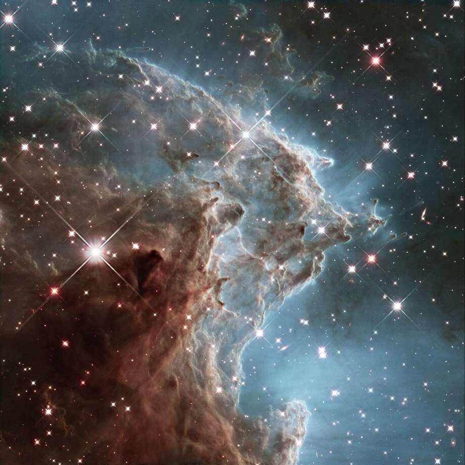 This image released on March 17, 2014 by the ESA and taken by the NASA/ESA Hubble Space Telescope shows the Monkey Head Nebula or NGC2174, to celebrates its 24th year in orbit. NGC 2174 lies about 6,400 light-years away in the constellation of Orion (The Hunter). Hubble previously viewed this part of the sky back in 2011 the colorful region is filled with young stars embedded within bright wisps of cosmic gas and dust. This portion of the Monkey Head Nebula was imaged in the infrared using Hubble's Wide Field Camera 3. Photo: HO / AFP /Getty Images / AFP