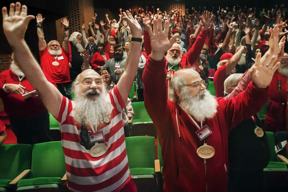 "Paul Akert of Wisconsin, left, and Thomas Bethke of Minnesota, right, raise their hands in the air and stretch alongside about 300 of their fellow ""Santas"" during the 82nd annual Charles W. Howard Santa Claus School Thursday, Oct. 3, 2019 at Midland Center for the Arts. (Katy Kildee/kkildee@mdn.net) Photo: (Katy Kildee/kkildee@mdn.net)"