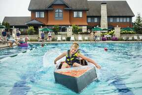 Drew Dittenber, 9, races his boat across the swimming pool at the Midland Country Club during a cardboard regatta Tuesday, Aug. 20, 2019. (Katy Kildee/kkildee@mdn.net)