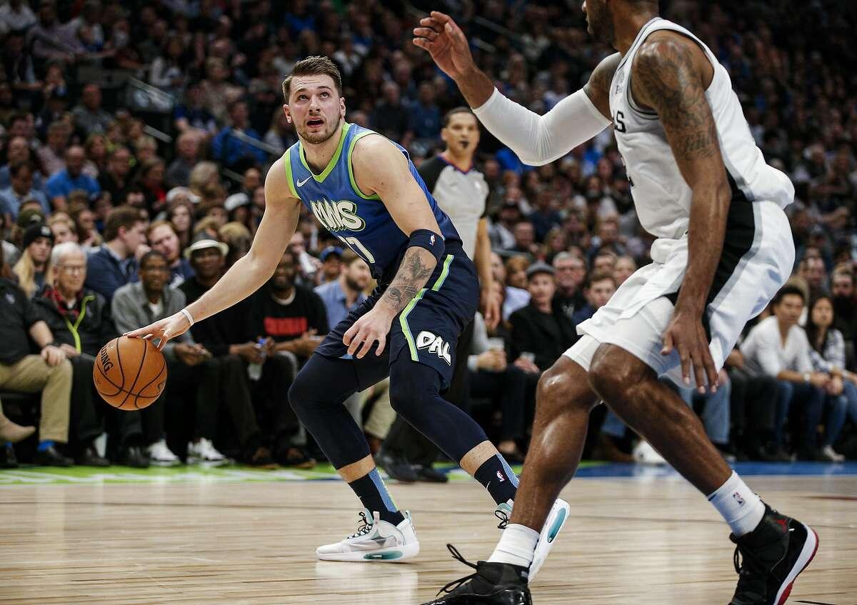 Dallas Mavericks forward Luka Doncic (77) looks for room against San Antonio Spurs forward LaMarcus Aldridge (12) during the first half of an NBA basketball game, Thursday, Dec. 26, 2019, in Dallas. Dallas won 102-98. (AP Photo/Brandon Wade)