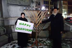 Rabbi and mrs. Morrison standing by the menorah at the public lighting