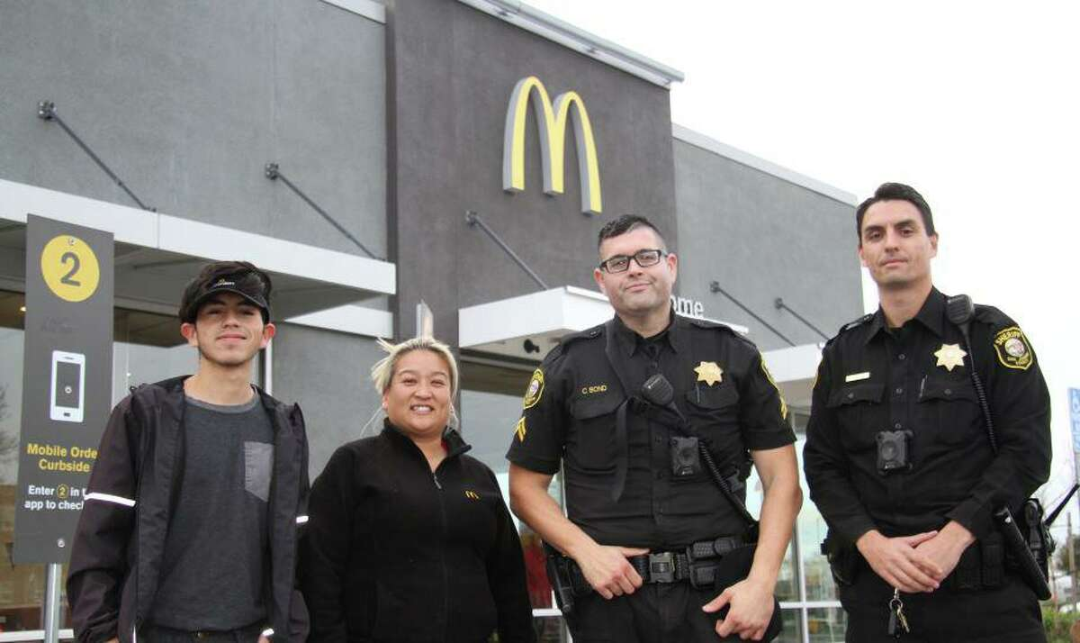 """McDonald's workers in Lodi pose with San Joaquin Sheriff's deputies after helping save a woman who mouthed the words """"help me"""" in the drive-thru line."""