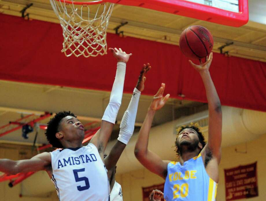 Kolbe Cathedral's Jalen Sullivan lays up the ball as Amistad's Jaden Ratliff defends during the Robert Saulsbury Basketball Invitational in New Haven on Friday. Photo: Christian Abraham /Hearst Connecticut Media / Connecticut Post