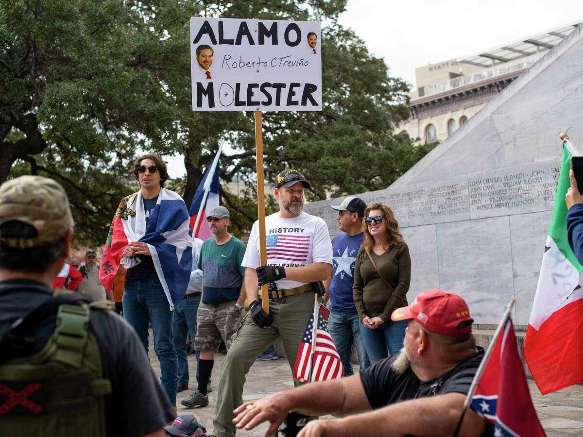 """Agustin Qui-ones, originally from New York but a Texas state resident since 1999, holds a sign opposing City Councilor Robert Trevi-o, as he stands in front of the Alamo Cenotaph in San Antonio, Texas, on Friday, December 27, 2019. Members of This is Texas Freedom Force are opposing the planned moving of the Alamo Cenotaph by the city of San Antonio. Qui-ones says that removing the monument is akin to removing a part of Texas?• history?'in this case the Battle of the Alamo?' that occurred on this very spot. He also cites the cost of moving the monument when asked why he opposes the move. ?'We?•re here today to occupy around the Cenotaph to stop any plans moving forward, trying to disassemble it and move it,?"""" Brandon Burkhart, president of This is Texas Freedom Force (TITFF) said. TITFF is asking that Texas citizens be allowed to vote on the removal of the monument to the Battle of the Alamo and to those soldiers who died there, citing that the cost of movement and repair if it is damaged will cost Texas taxpayers."""