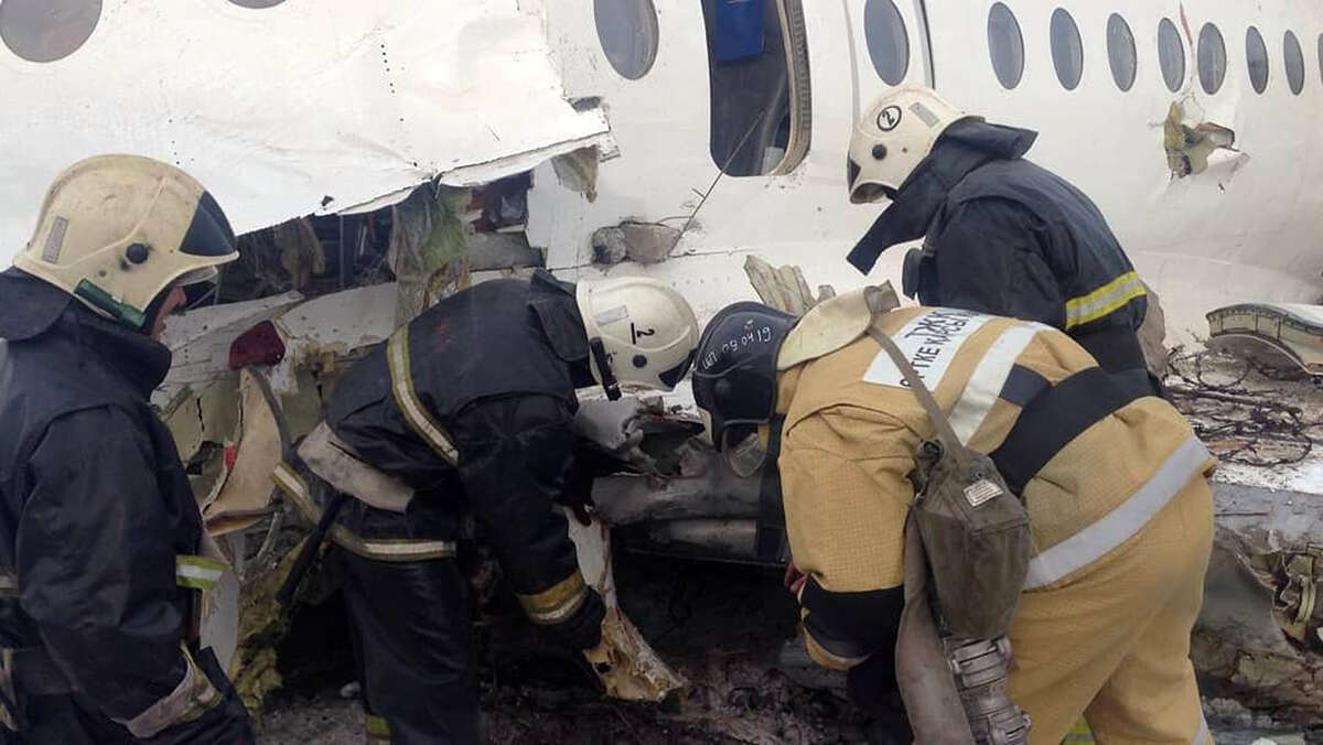 """This handout picture taken on December 27, 2019 and released by Kazakhstan's emergencies committee shows rescuers working at the site of a passenger plane crash outside Almaty. - At least 15 people died and dozens were injured on December 27, 2019 when a passenger plane carrying 100 people crashed shortly after takeoff from Kazakhstan's largest city and slammed into a house, state media reported. (Photo by HO / Kazakhstan's emergencies committee / AFP) / RESTRICTED TO EDITORIAL USE - MANDATORY CREDIT """"AFP PHOTO / Kazakhstan's emergencies committee"""" - NO MARKETING - NO ADVERTISING CAMPAIGNS - DISTRIBUTED AS A SERVICE TO CLIENTS (Photo by HO/Kazakhstan's emergencies committ/AFP via Getty Images)"""