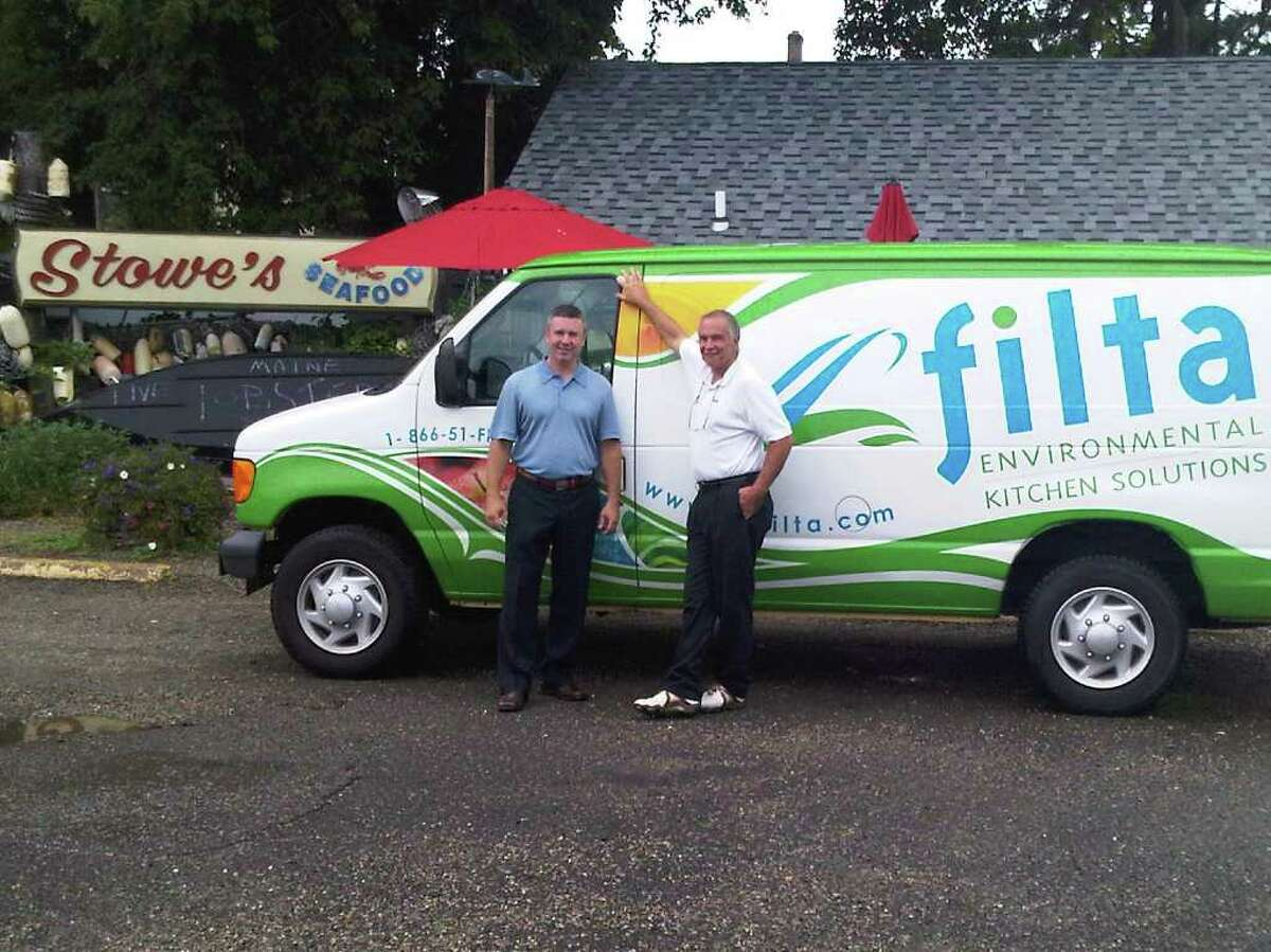 Matt Neeley and Neil Groglio, co-owners of a Filta franchise in Shelton, in front of their first customer, Stowe's Seafood in Stratford.